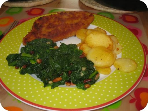 Spinazie met pijnboompitten, kipschnitzel en aardappelschijfjes