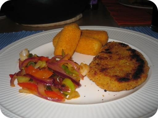 een kipschnitzel met gewokte groenten in zoetzure saus en aardappelkroketjes