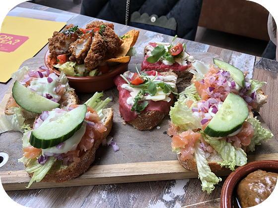 Lunchen bij Tr3s Veenendaal salade met pikante kip, nacho snippers en chili dressing, broodjes met carpaccio met parmezaan en truffelmayonaise en broodjes zalmtartaar met rode ui en wasabi mayonaise.